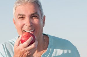 man with dentures biting apple