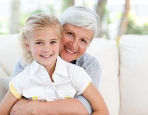 portrait of smiling grandmother and granddaughter in their home